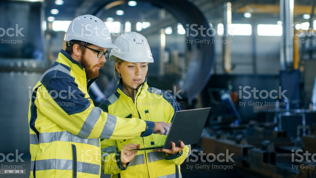 Male and Female Industrial Engineers in Hard Hats Discuss New Project while Using Laptop. They Make Showing Gestures.They Work in a Heavy Industry Manufacturing Factory. stock photo