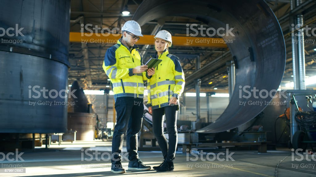 Male and Female Industrial Engineers in Hard Hats Discuss New Project while Using Tablet Computer. They Make Showing Gestures.They Work at the Heavy Industry Manufacturing Factory. stock photo