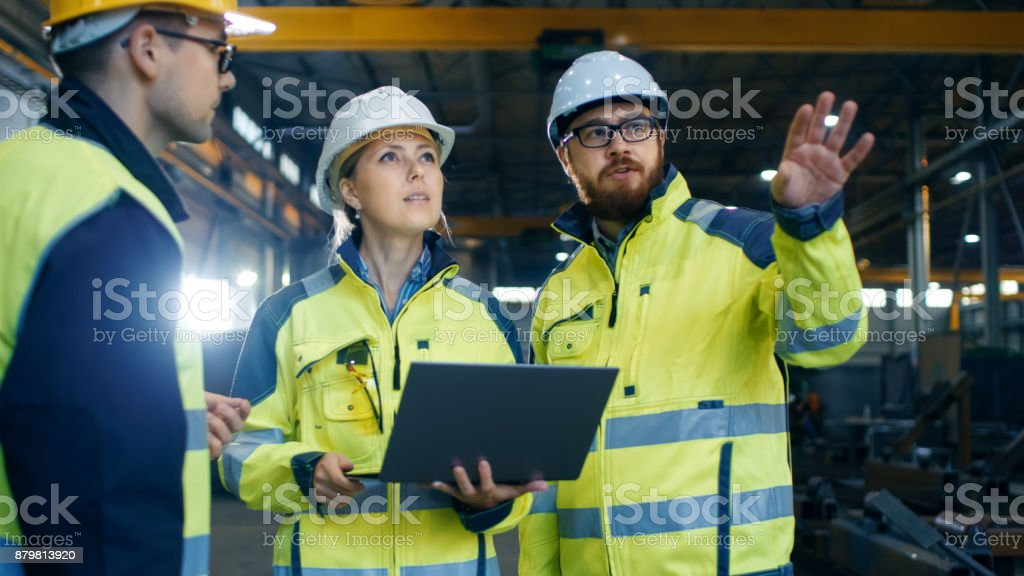 Male and Female Industrial Engineers Talk with Factory Worker while Using Laptop. They Work at the Heavy Industry Manufacturing Facility. stock photo