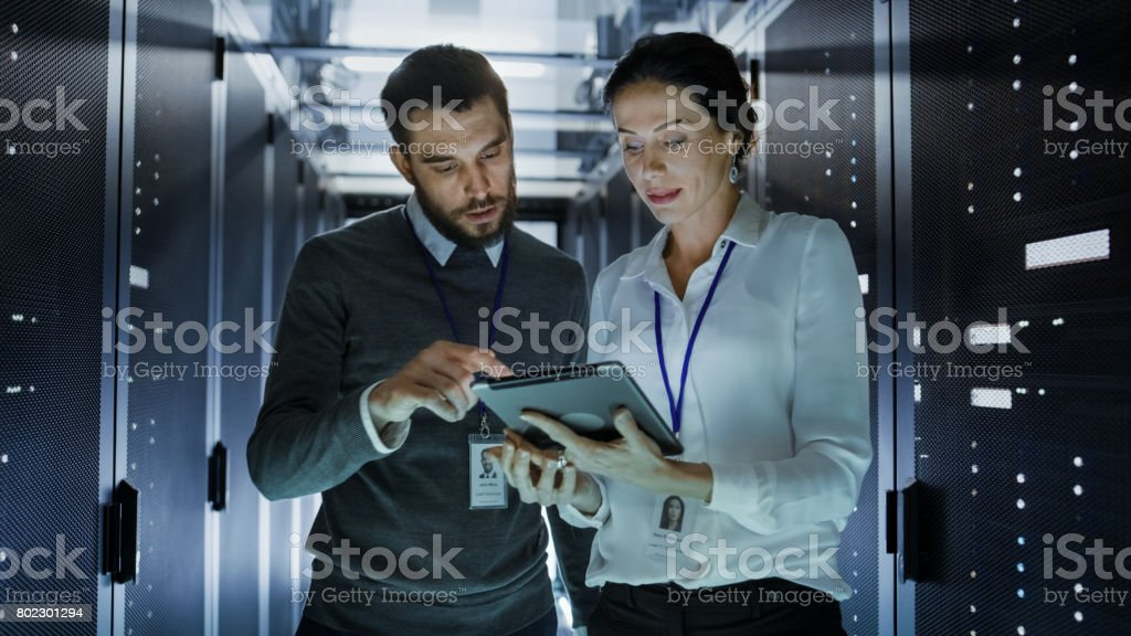 Male and Female IT Engineers in Data Center / Server Room, They are Talking. One of them Holds Tablet Computer. stock photo