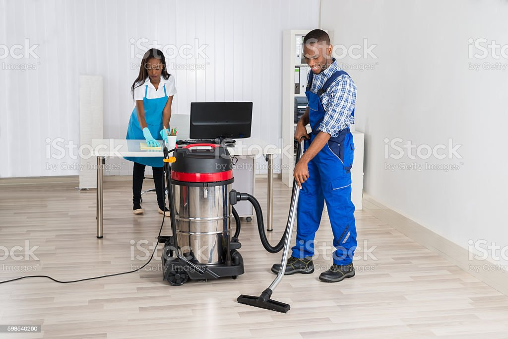 Male And Female Janitor Cleaning Office photo libre de droits