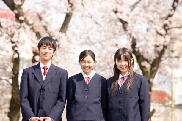 桜の花の下で笑っている男性と女性高校生 - 制服 ストックフォトと画像