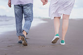 male and female legs in sports shoes walk along the beach against the background of the sea. vacation, love, family concept.