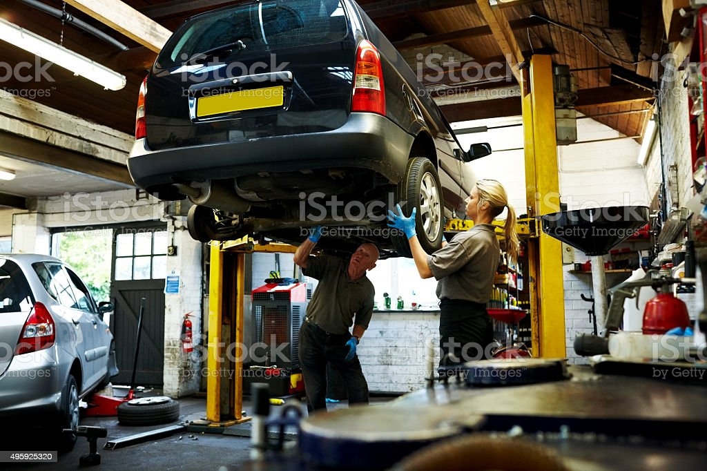 Male and female mechanics working on a car in garage stock photo