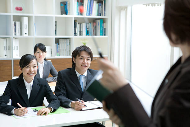 Male and female new employees gaining on-the-job training stock photo