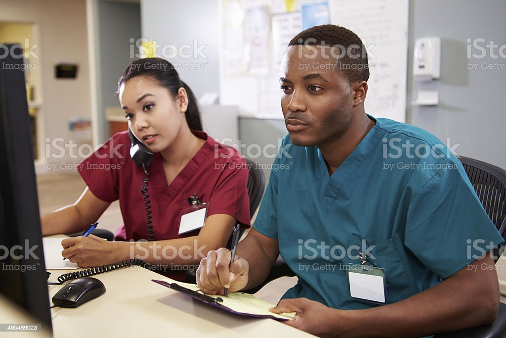 Masculino e enfermeira trabalhando na estação de enfermagem - foto de acervo