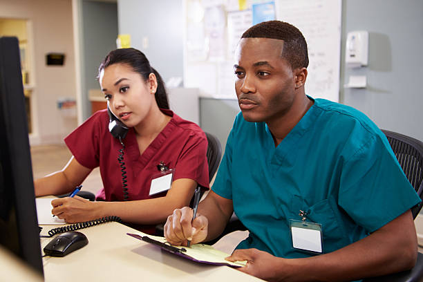 male and female nurse working at nurses station - nurse on phone stock photos and pictures