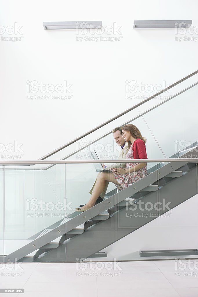Male and female office workers conversing while using laptop on stairs royalty-free stock photo