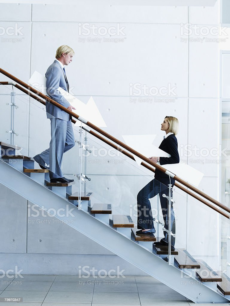 Male and female office workers on staircase holding arrow signs stock photo
