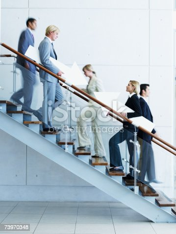istock Male and female office workers on staircase holding arrow signs 73970348