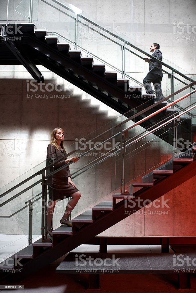 Male and Female Office Workers Walking Up Staircase stock photo