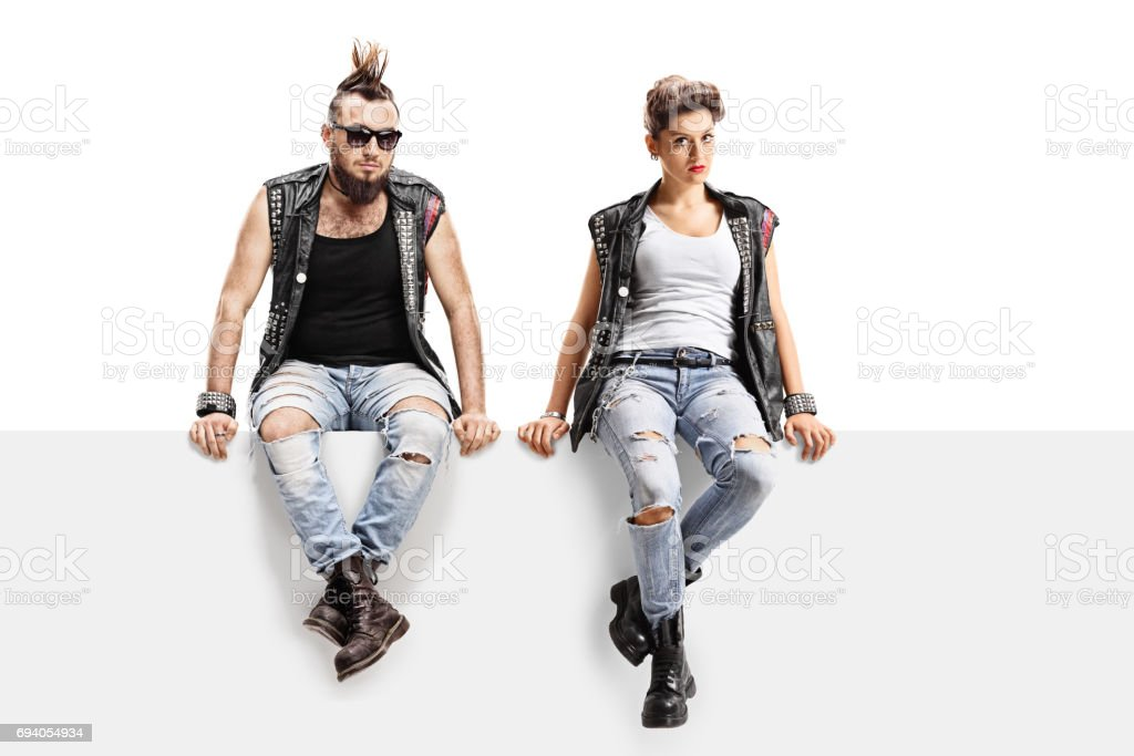 Male and female punkers sitting on a panel stock photo