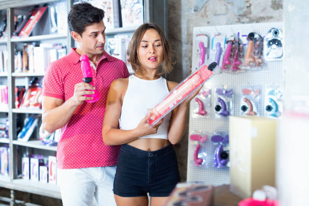 male and female purchasers touching big dildo in the modern sex shop Glad positive  male and female purchasers touching big dildo in the modern sex shop sex toy stock pictures, royalty-free photos & images