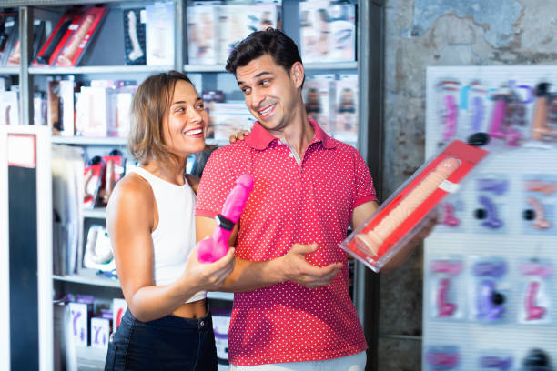 male and female purchasers touching big dildo in the modern sex shop Glad  positive smiling male and female purchasers touching big dildo in the modern sex shop sex toy stock pictures, royalty-free photos & images