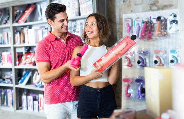male and female purchasers touching big dildo in the modern sex shop Glad  male and female purchasers touching big dildo in the modern sex shop dildo stock pictures, royalty-free photos & images