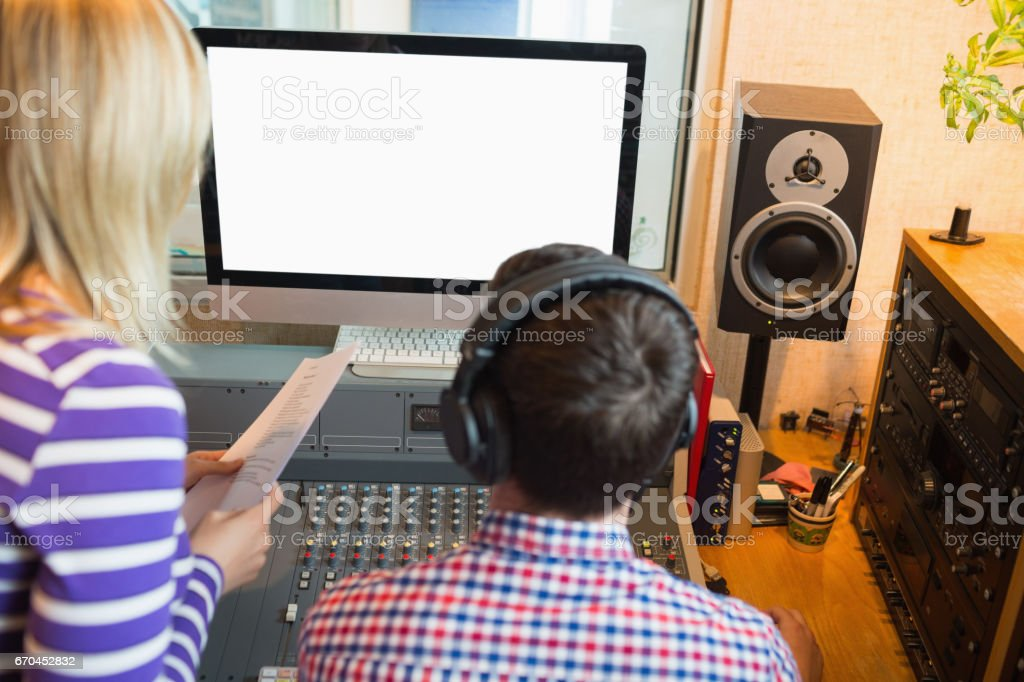 Male and female radio hosts in studio stock photo