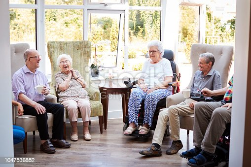istock Male And Female Residents Sitting In Chairs And Talking In Lounge Of Retirement Home 1047536852