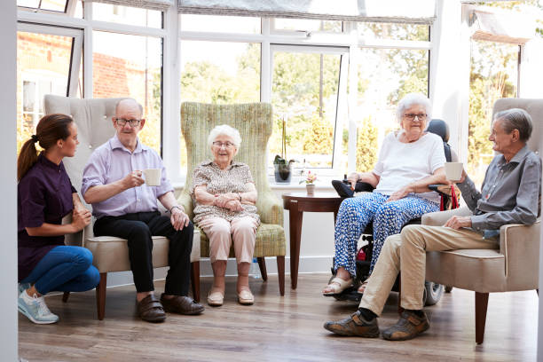 Male And Female Residents Sitting In Chairs And Talking With Carer In Lounge Of Retirement Home Male And Female Residents Sitting In Chairs And Talking With Carer In Lounge Of Retirement Home retirement community stock pictures, royalty-free photos & images