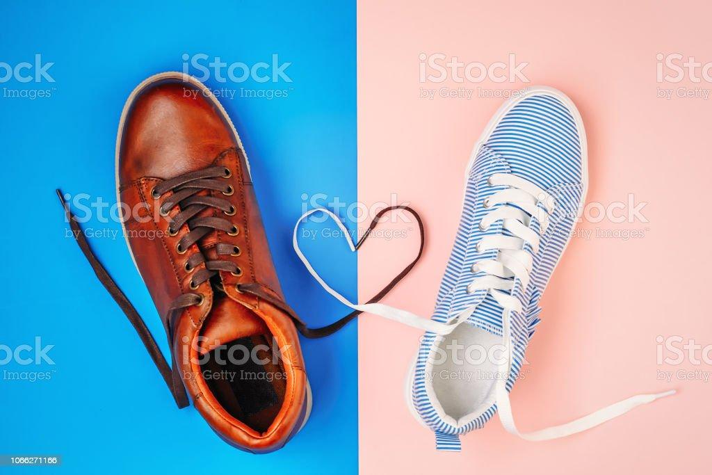 35c8abe317 Sapatos masculinos e femininos em fundo azul e rosa com cadarços em forma  de coração,