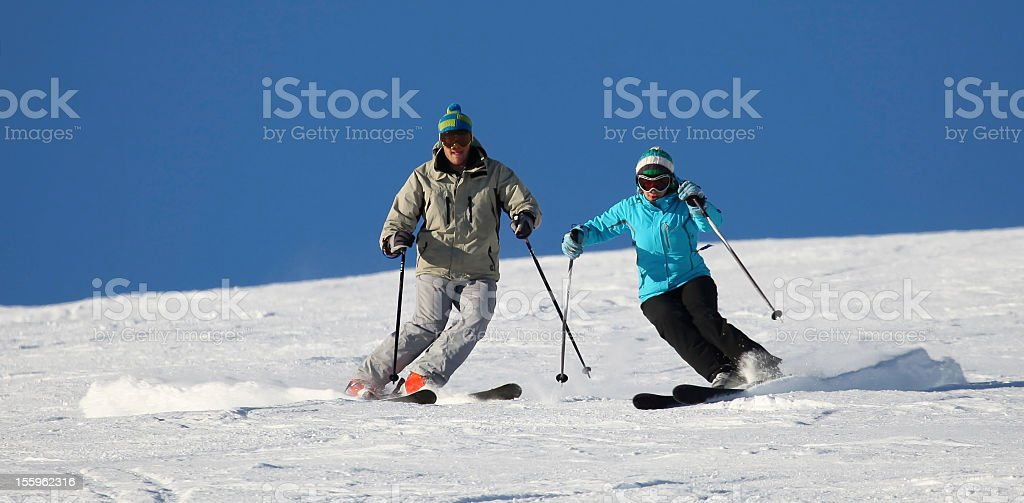 Male and female skiers on packed powder snow royalty-free stock photo