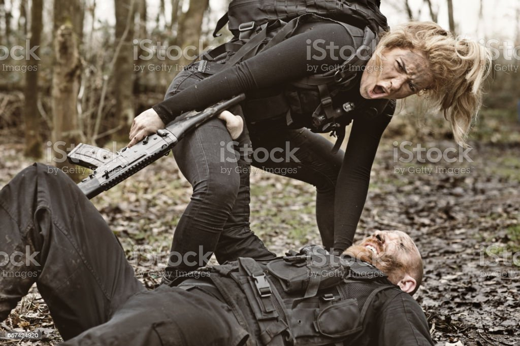 Male and Female Soldiers in Military Shoot in woodlands stock photo