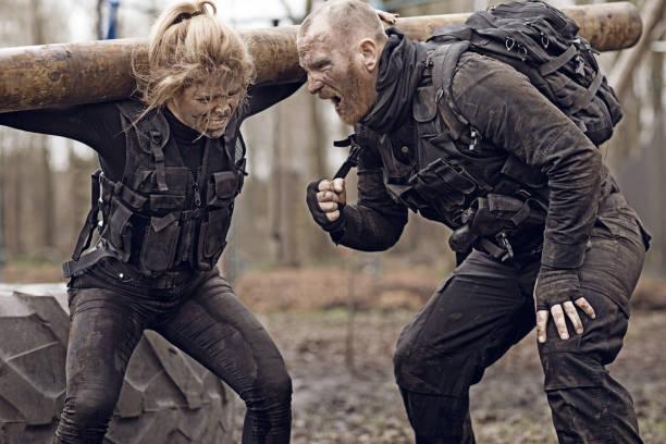 männliche und weibliche soldaten in militärischen schießen in waldgebieten - militärisches training stock-fotos und bilder