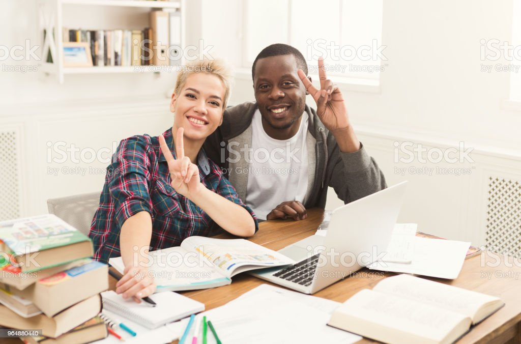 Male and female students at table full of books royalty-free stock photo