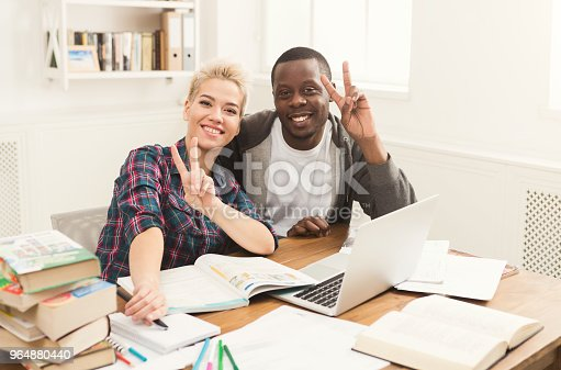 1009493672istockphoto Male and female students at table full of books 964880440