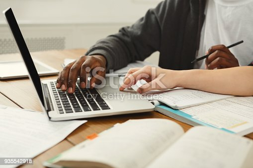 1009493672istockphoto Male and female students at wooden table full of books 935542918