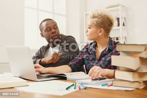 1009493672istockphoto Male and female students at wooden table full of books 936144446