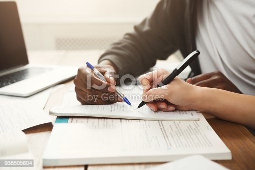 1009493672istockphoto Male and female students at wooden table full of books 938505604