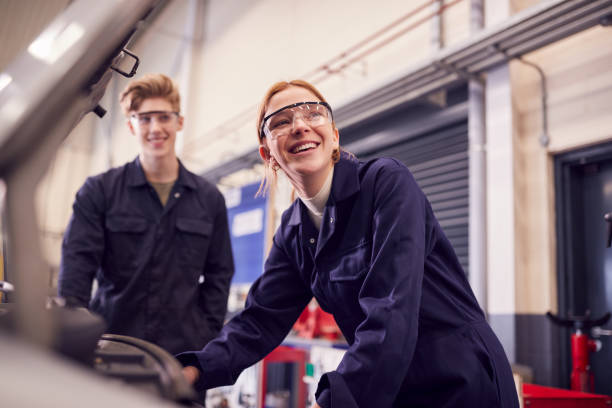 Male And Female Students Looking At Car Engine On Auto Mechanic Apprenticeship Course At College stock photo