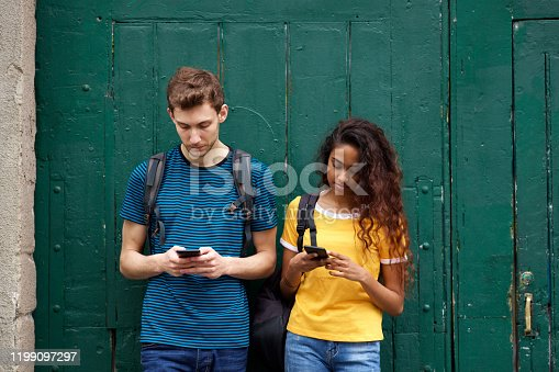 Portrait of male and female students looking at mobile phone with serious expression