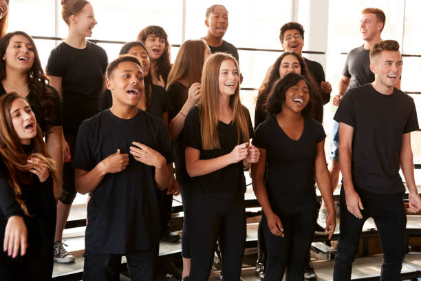 Male And Female Students Singing In Choir At Performing Arts School Male And Female Students Singing In Choir At Performing Arts School performing arts event stock pictures, royalty-free photos & images