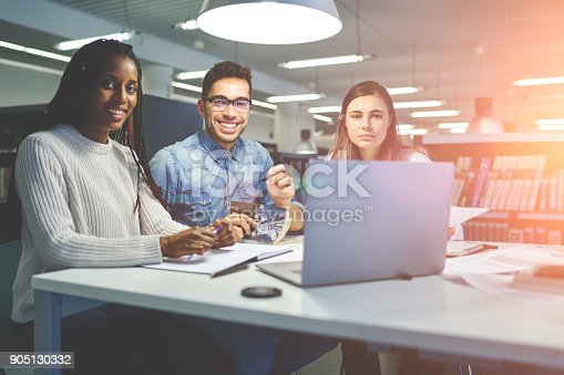 905130626 istock photo Male and female students working in group making researches and analyzing information on informal meeting, portrait of smiling skilled co-workers enjoying collaboration in friendly atmosphere 905130332
