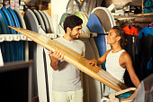 smiling male and female surfers holding surfboard in the shop