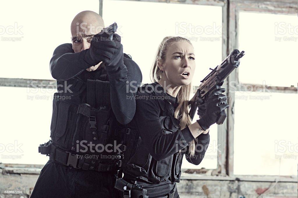 Male and Female swat team members working in urban setting