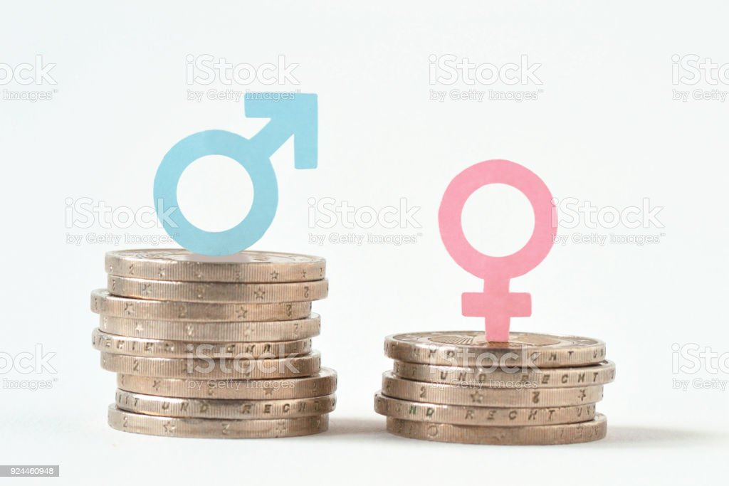 Male and female symbols on piles of coins - Gender pay equality concept stock photo