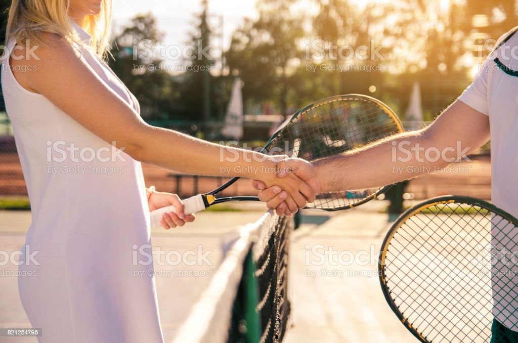 Male and female tennis players shaking hands on net stock photo