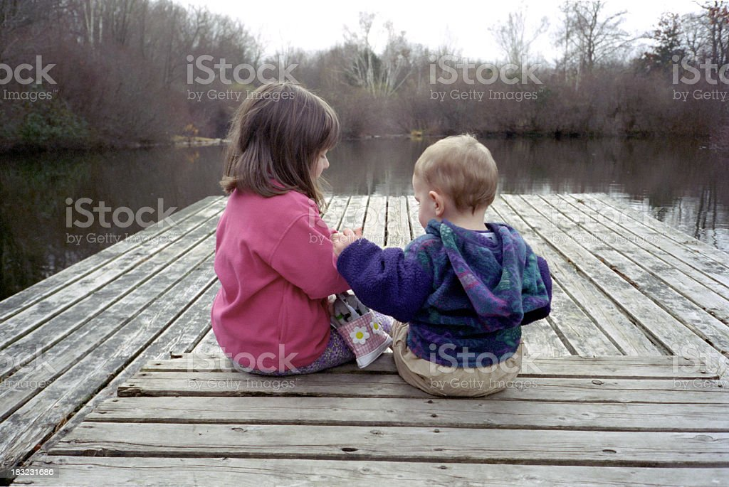 Male and female toddlers on a wooden dock facing a lake royalty-free stock photo