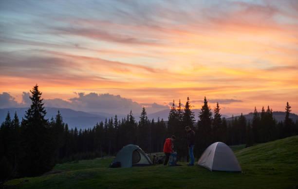 männliche und weibliche touristen auf dem campingplatz in der nähe von zwei zelten in den bergen beim wandern zusammen mit ihren rucksäcken. auf dem hintergrund schöne sonnenuntergang mit feurigen bunten himmel beziehungen natur - zelt stehhöhe stock-fotos und bilder