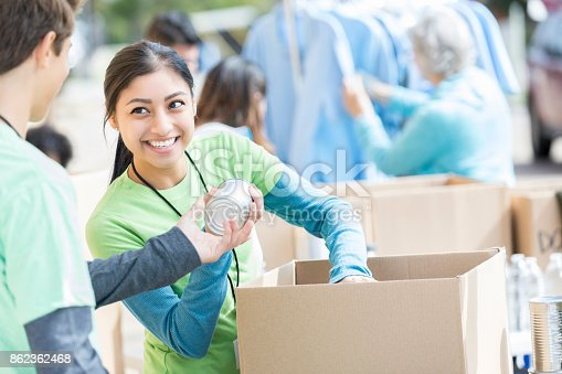 istock Male and female volunteers sort donations during food drive 862362468