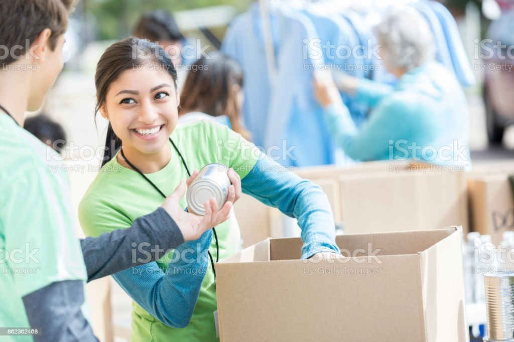 Male and female volunteers sort donations during food drive stock photo