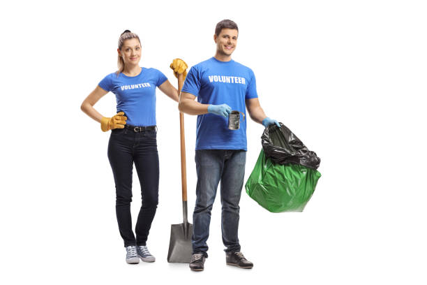 Male and female volunteers with a spade and garbage bag stock photo
