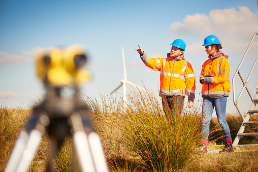 two wind farm engineers using a builder's level to plan out the expansion of the wind farm site. they are wearing orange hi vis jackets and blue hard hats . one is male , one is female. In the foreground the female is looking through the level whilst the male engineer is approaching .In the background wind turbines can be seen across the landscape.