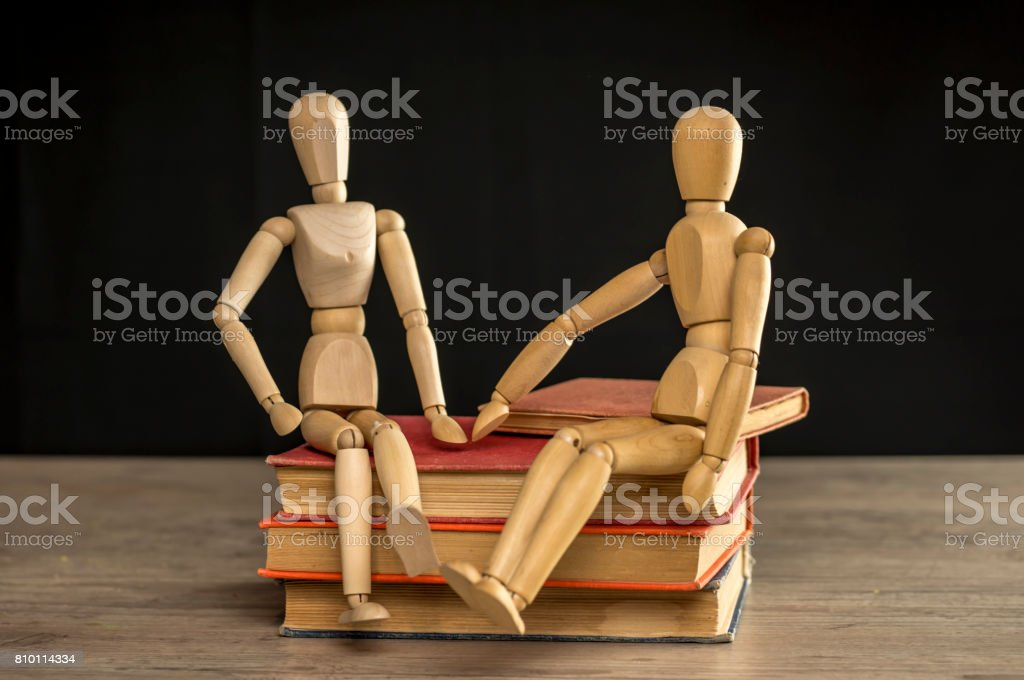 Male and female wooden mannequins sitting on books stock photo