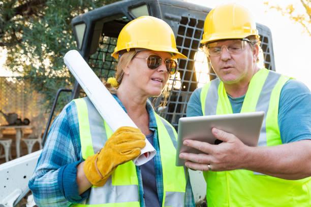 Arbeitnehmerinnen und Arbeitnehmer mit technischen Baupläne und Computer Tablet sprechen auf Baustelle – Foto