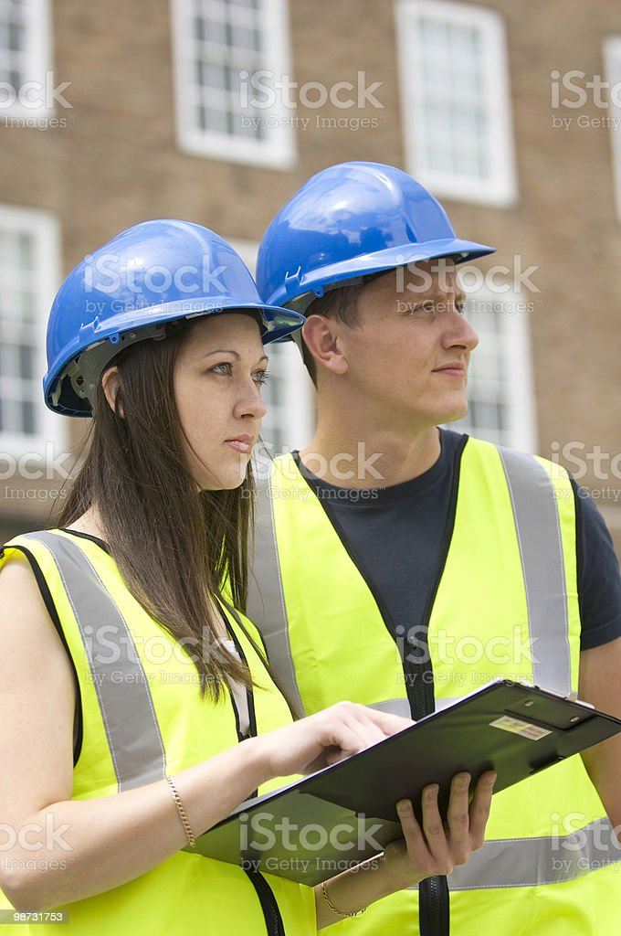Male and female young construction engineers view a site 免版稅 stock photo