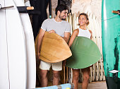 smiling male and woman surfers holding surfboard in the shop