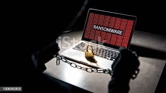 686526046istockphoto Male anonymous hacker locking computer by using chain and padlock. Cyber attack and Internet data security concept 1006062820